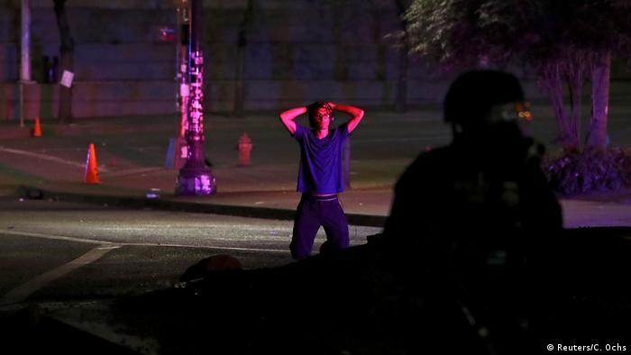 Demonstrant kniet sich, als ein Bundespolizist sich nähert