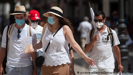Tourists wearing face masks walk along the Marques de Larios street in Malaga
