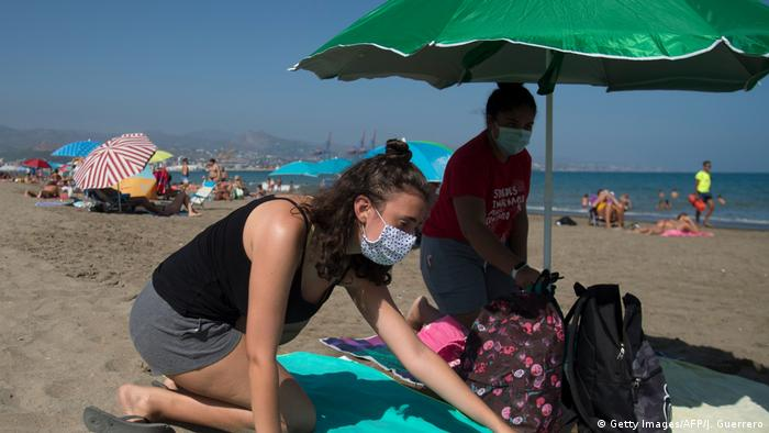 Two holidaymakers wear masks on a beach in Spain