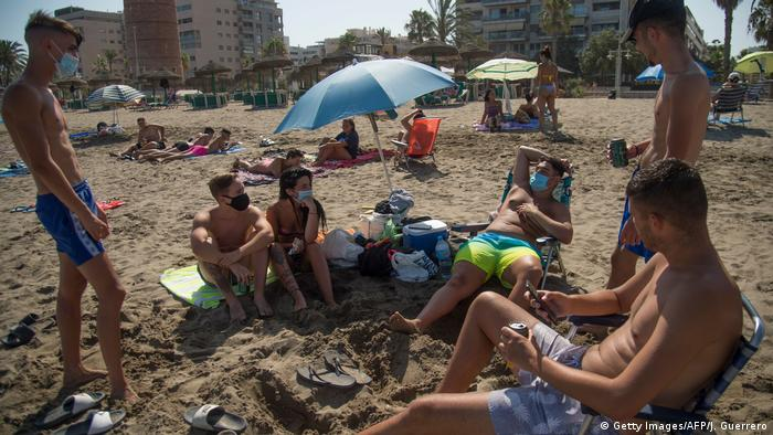 A group of people wear masks on a Spanish beach