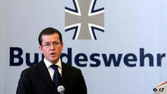 Defense Minister Guttenberg at a press conference with the Bundeswehr logo behind him