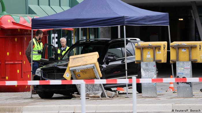 Officials stand next to the vehicle which crashed into a group of people in Berlin