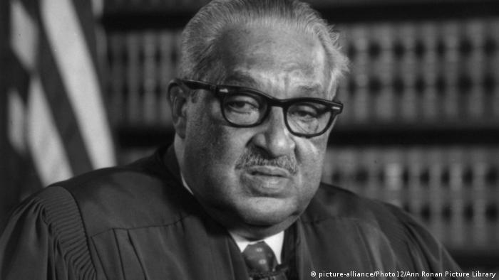 Thurgood Marshall, pictured wearing his judicial robes in front of a bookshelf
