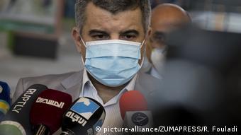 Iradsch Harirchi mit Maske vor Mikrofonen