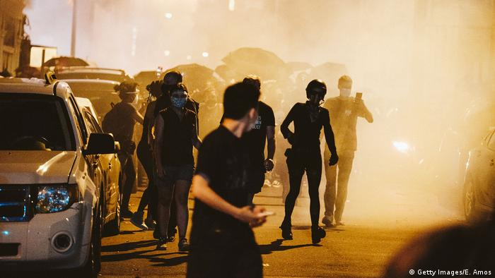 Demonstranten im Gegenlicht, die vor Tränengaswolken davonlaufen