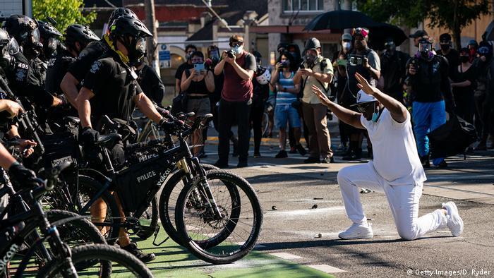 Ein Schwarzer Mann kniet vor Polizisten mit Fahrrädern