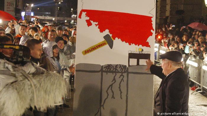Berlin 2009: Lech Wałęsa przewraca kostki domina symbolizujące mur berliński
