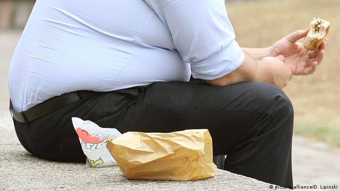 Overweight man eating a hamburger (picture-alliance/D. Lipinski)