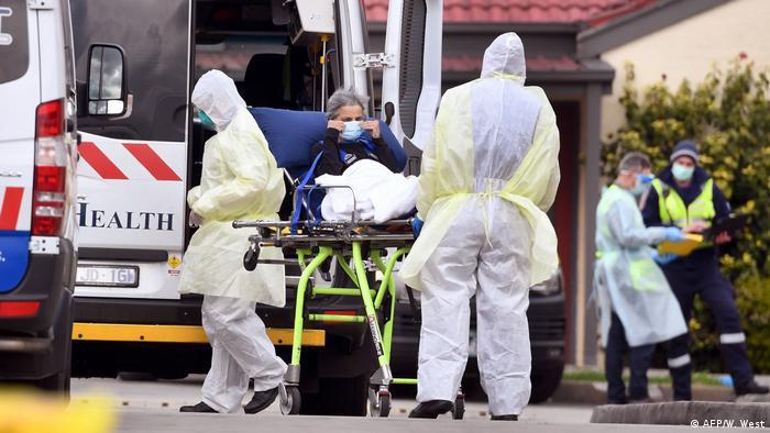 Medizinisches Personal in Schutzkleidung transportiert eine Frau in einen Rettungswagen (AFP/W. West)