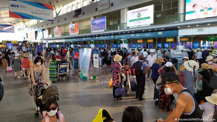 Menschen warten mit Mund-Nasen-Masken in einer Flughafenhalle (Reuters/VNA/Tran Le Lam)