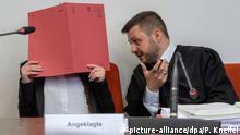 ARCHIV - 09.04.2019, Bayern, München: Die Angeklagte hält auf ihrem Sitz im Gerichtssaals einen roten Aktendeckel vor ihr Gesicht. Rechts spricht ihr Anwalt Ali Aydin mit ihr. Der Frau wird unter anderem vorgeworfen, ein fünf Jahre altes Mädchen als Sklavin gehalten und verdursten lassen zu haben. Der Prozess begann im April 2019 und sollte eigentlich schon im September enden. Inzwischen hat das Gericht aber bis zum 4. Mai 2020 nachterminiert. Foto: Peter Kneffel/dpa +++ dpa-Bildfunk +++ | Verwendung weltweit