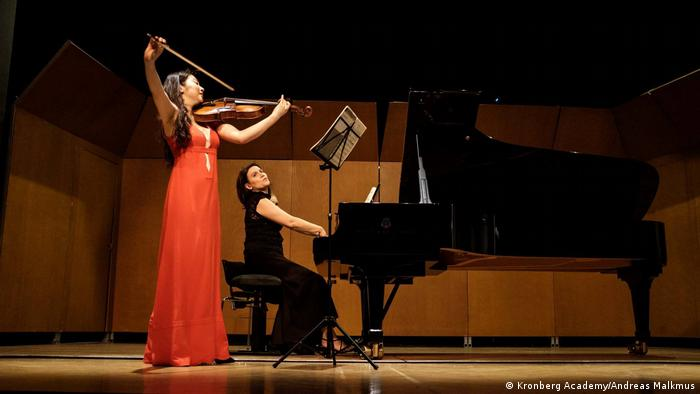 Wearing a red gown, Hwayoon Lee holds her violin dramatically during the Young Euro Classic Ztou Orchestra Festival in Berlin