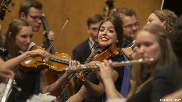 A young woman playing a stringed instrument looks up during an orchestra performance