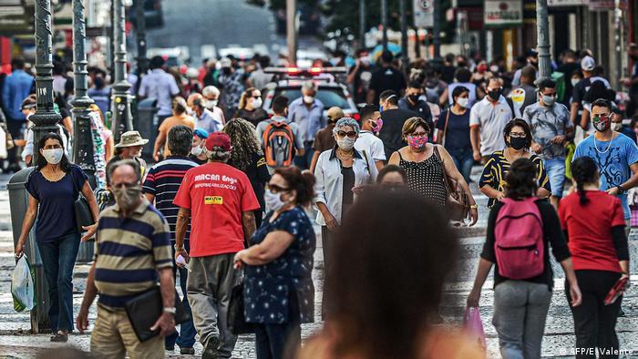Pessoas de máscara em rua comercial em Florianópolis