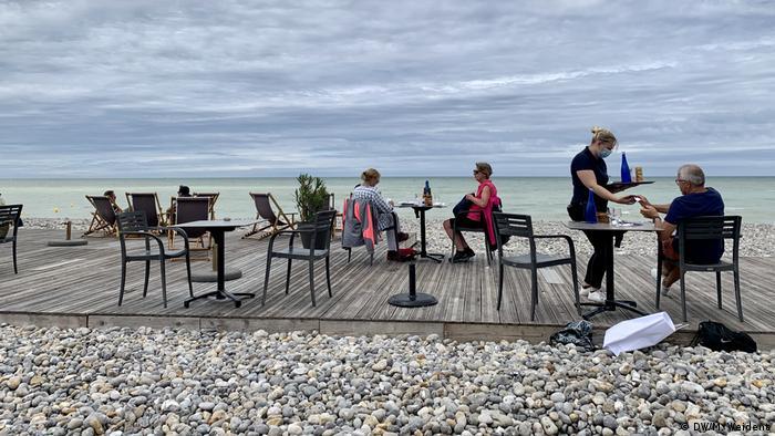 Mesas próximas ao mar. Garçonete, de máscara, serve um senhor, sentado sotinho em uma mesa. Duas senhoras estão sentadas em outra mesa.