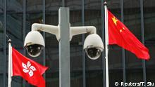 Hong Kong and Chinese national flags are flown behind a pair of surveillance cameras