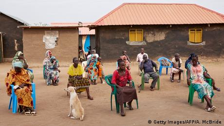 People sitting outside in an African village, listening to a presentation about coronavirus hygiene.
