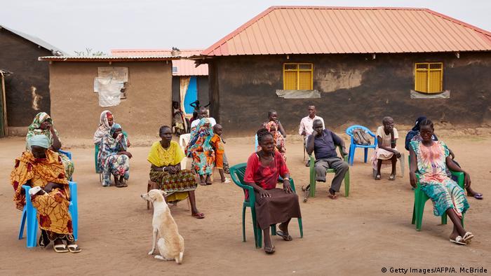 Una comunidad rural en África se sienta al aire libre guardando la distancia