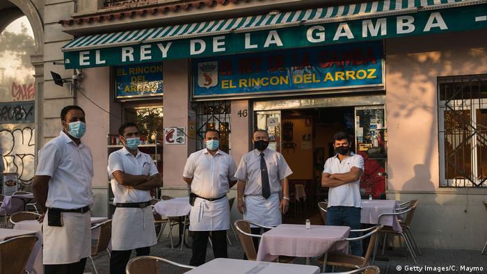 Fünf Kellner mit Schutzmasken stehen vor leeren Tischen vor einem Restaurant in Barcelona