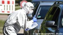 27.07.2020 *** A tester gestures with to driver in a coronavirus COVID-19 car testing station for residents in Mamming, southern Germany, after an outbreak of COVID-19 coronavirus at a farm on July 27, 2020. - A total of 174 seasonal workers on a large Bavarian farm in the municipality of Mamming have tested positive for the coronavirus COVID-19 and some 500 are in quarantine to contain a mass coronavirus outbreak. (Photo by Christof STACHE / AFP) (Photo by CHRISTOF STACHE/AFP via Getty Images)
