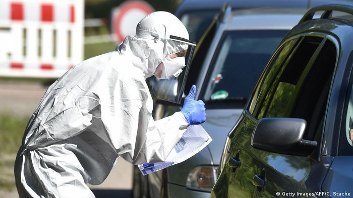 Mann in weißem Schutzanzug steht an der Drive-in-Teststation in der bayerischen Gemeinde Mamming neben einem Auto (Getty Images/AFP/C. Stache)