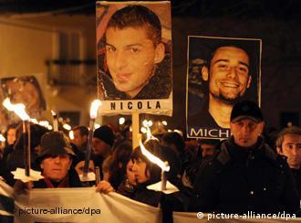 Bei einer Lichtertprozession in L'Aquila werden Plakate mit Fotos der Erdbebenopfer hochgehalten (Foto: dpa)
