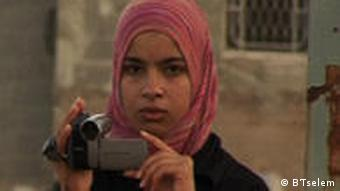 A Palestinian girl uses a video camera to document abuse and misconduct by Israeli forces in the West Bank as part of the project by human rights NGO B'Tselem