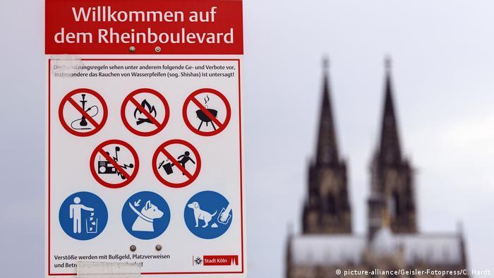 Symbolfoto Verbotskultur, Verbotsschild mit diversen Verboten wie nicht rauchen, kein Feuer machen, nicht grillen, keine laute Musik, dahinter verschwommen der Kölner Dom
