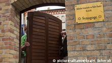 28.07.2020, Sachsen-Anhalt, Halle (Saale): Thomas Thiele (l), Tischlermeister, und seine Mitarbeiter montieren die Tür zum Grundstück der Synagoge Halle/Saale. Thiele hatte die alte Tür einst für die Synagoge gefertigt. Sie erlangte am 09. Oktober 2019 traurige Berühmtheit, als der Attentäter von Halle in die Synagoge eindringen wollte. Er schoss mehrfach auf die Holztür, scheiterte allerdings. Jetzt wird die neue, vom Aussehen identische, aber sicherere Tür eingebaut. Foto: Hendrik Schmidt/dpa-Zentralbild/dpa +++ dpa-Bildfunk +++ | Verwendung weltweit