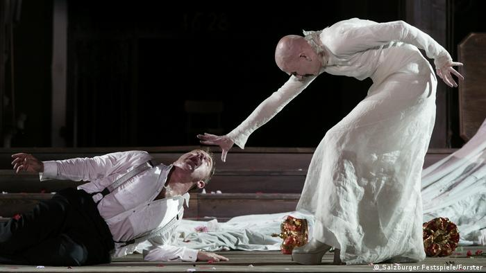 Two men, one lying on his side, the other holding his hand over his head as though putting him under a spell (Salzburger Festspiele/Forster)