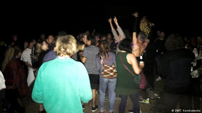 Junge Leute stehen auf einer Wiese in Berlin eng zusammen