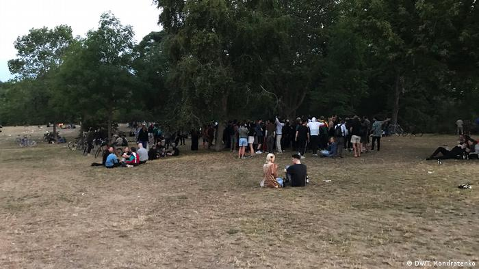 People dance and sit on the grass after the sun has risen