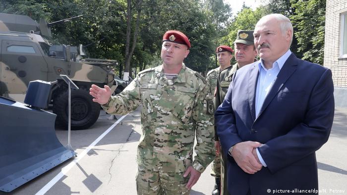 Alexander Lukaschneko steht neben Militärs vor gepanzerten Fahrzeugen (picture-alliance/dpa/N. Petrov)