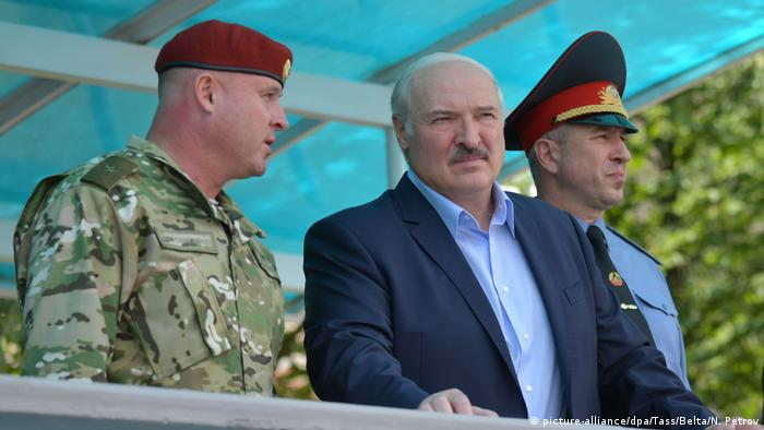 Alexander Lukashenko (center) flanked by two soldiers