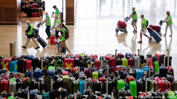 A group of volunteers walk past rows of suitcases.
