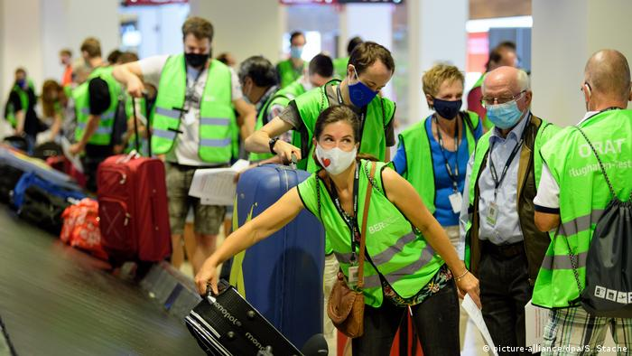 A volunteer tester takes her suticase from a luggage belt during the trial run.