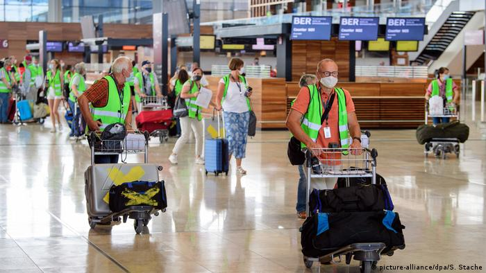 A group of volunteers with their suitcases on trolleys in the main terminal building