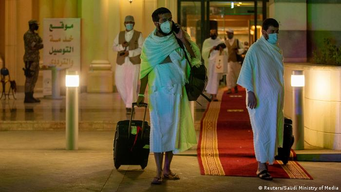Muslim pilgrims wear protective masks heading to the Meeqaat