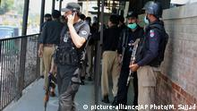 Police officers gather at an entry gate of district court following the killing of Tahir Shamim Ahmad, who was in court accused of insulting Islam, in Peshawar, Pakistan, Wednesday, July 29, 2020. A young Pakistani Muslim walked into a courtroom in the northwestern city of Peshawar and shot and killed a fellow Muslim Ahmad, who was on trial for blasphemy, a police officer said. (AP Photo/Muhammad Sajjad)