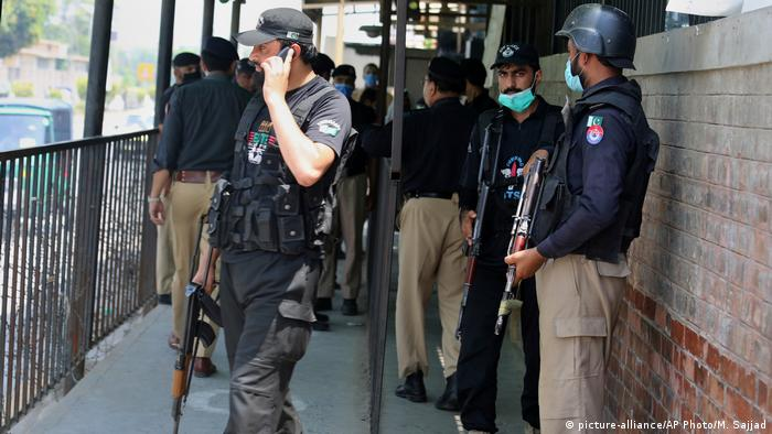 Police outside the court where a defendant was shot while on trial for blasphemy