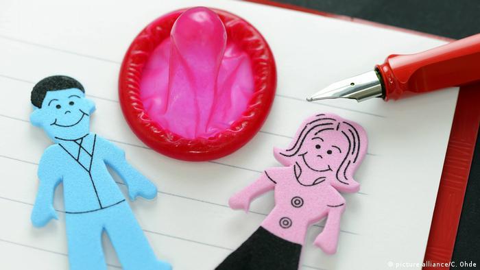 Figurine cu un bărbat și o femeie lângă un prezervativ