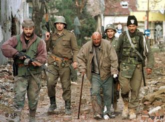 This is a November 18 1991 photo of Yugoslav army soldiers (background) and Serbian volunteers escorting a Croat civilian after they entered Vukovar in eastern Croatia. A landmark war crimes trial opened in Belgrade Tuesday, March 9, 2004, against six Serb suspects accused of killing 192 Croat prisoners of war at a pig farm during the 1991 war in the Balkans. (AP Photo/Srdjan Ilic)