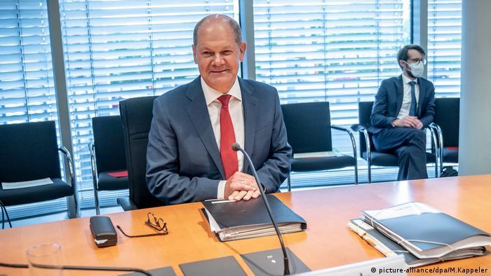 Finanzminister Olaf Scholz sitzt an einem Tisch mit Mikrofon, vor ihm liegt eine Aktenmappe (picture-alliance/dpa/M.Kappeler)