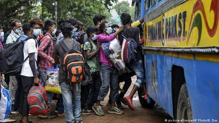 Commuters wearing face masks jostle for a ride on a bus discarding social distancing guidelines in Kolkata