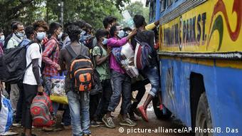 Люди толпятся возле рейсового автобуса в Калькутте