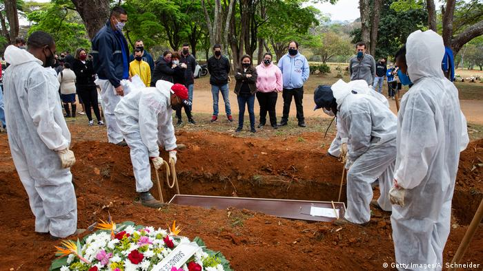 Relatives mourn as cemetery workers in protective suits bury a victim of coronavirus