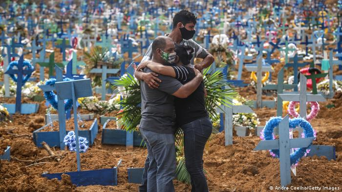 Relatives of a deceased person wearing protective masks mourn during a mass burial of coronavirus pandemic victims in Manaus