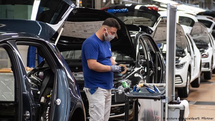 Funcionário, de máscara, em uma fábrica de carros.