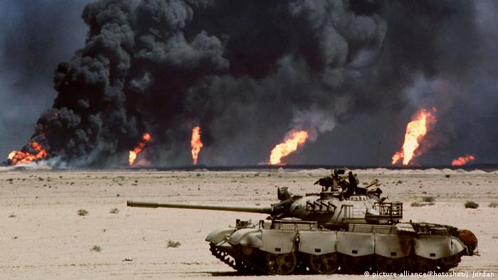 An abandoned tank in the desert in front of burning oil wells
