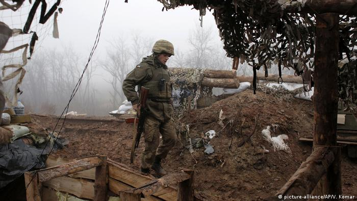 A Ukrainian soldier walks across muddy ground outside of a command post